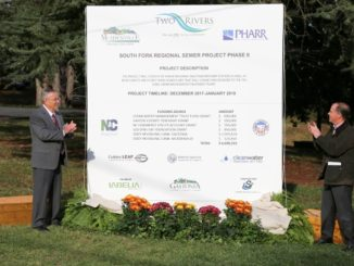 Dignitaries applauding next to the project sign
