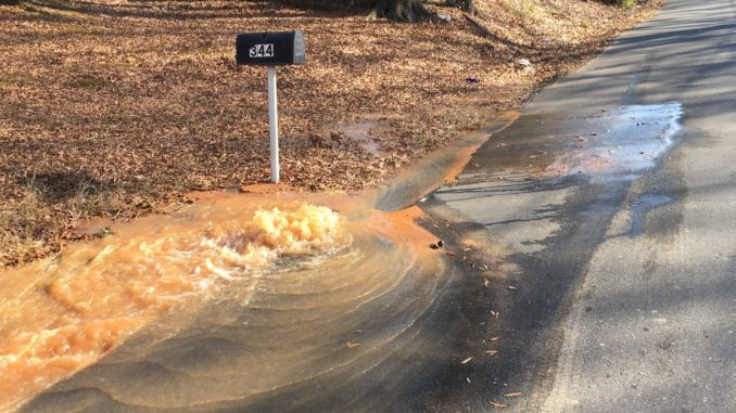 Water bubbling up onto street from leaking main
