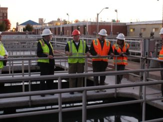 City council members in hard hats touring water plant