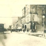 Photo of Main Avenue with horse-drawn carriages, cars and people. Around 1900.