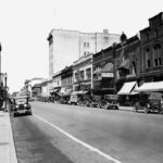Cars parallel parked along Main Avenue in 1929
