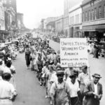 Protesters carrying a sign that says United Textile Workers of America, marching down Main Avenue 1929
