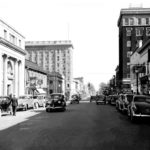 Cars parked along and driving on Main Avenue in 1938
