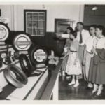 Five people looking at a display of tires