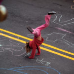 Girl doing handstand in street with sidewalk-chalk drawings around her