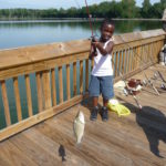 Young boy has caught a fish while fishing at Rankin Lake