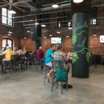 People eating and drinking at Growler USA in former Loray Mill
