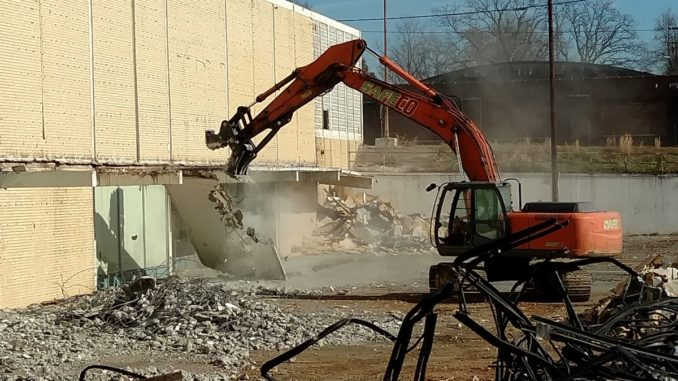 Equipment demolishing the side of a building