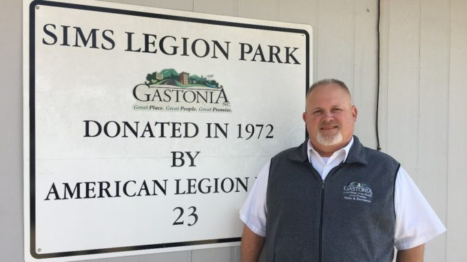 Cam Carpenter stands next to Sims Legion Park sign