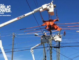 Linemen working way above ground on electric lines. RP3 logo on side.