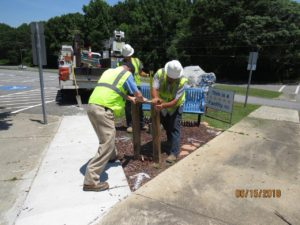 Men in hard hats installing posts into ground