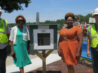 City and school officials alongside Little Free Library