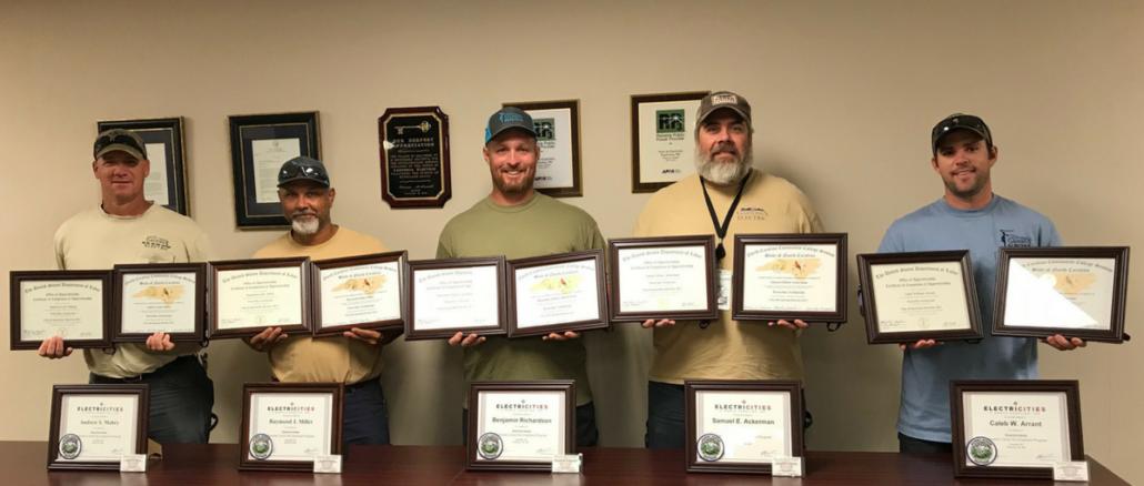 Five men holding framed certificates