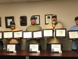 Five men holding framed certificates