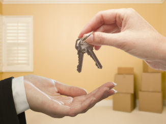 Two hands exchanging keys representing a new homebuyer