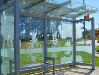 Bus shelter with etched glass showing people jogging, biking and sitting on a park bench