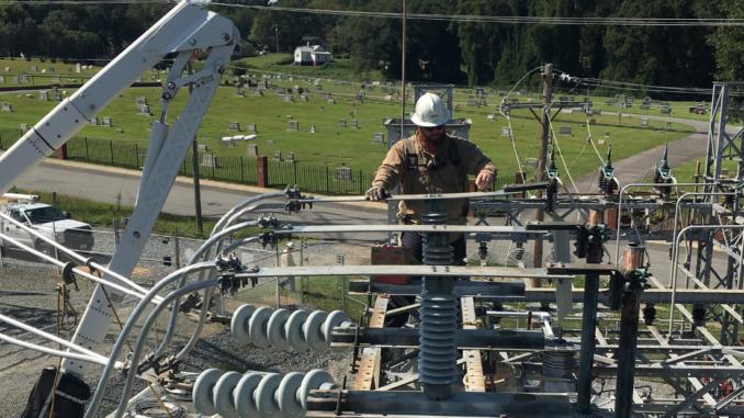 Man wearing hardhat repairing electric substation