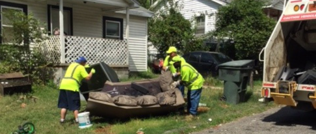 Crews in yellow vests lifting an old couch into a garbage truck