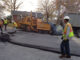 Six men using heavy equipment and tools to repave a street