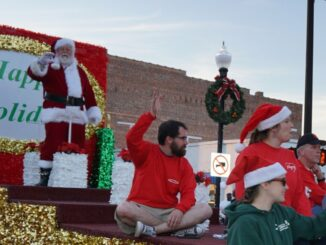 Santa standing on a float in a parade