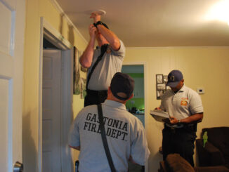 Firefighters installing smoke detector