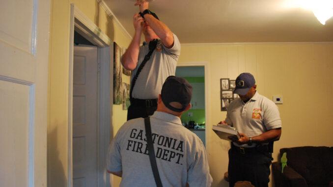 Firefighters installing smoke detector