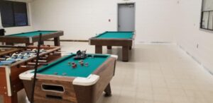 Pool tables in room with old flooring