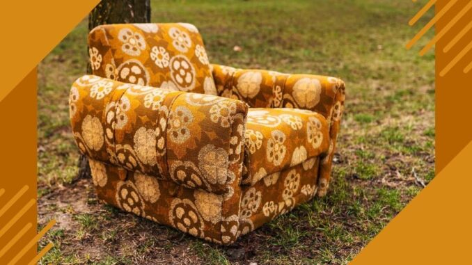 Upholstered chair with bright yellow and brown flowered print fabric