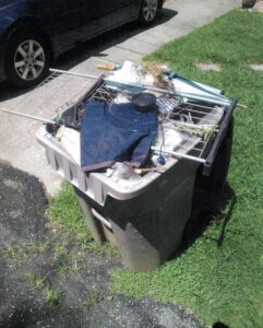 Recycling bin filled with trash including discarded clothing