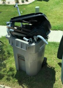 Dismantled lawn chair in recycle bin