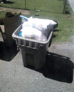 Recycling bin stuffed with bagged trash