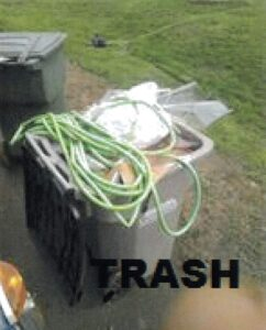 Recycling bin filled with trash and garden hose