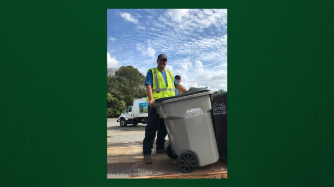Man picking up gray recycling cart