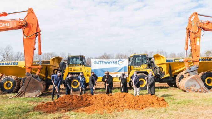 Gastonia City Councilmembers with shovels and dirt in front of heavy equipment