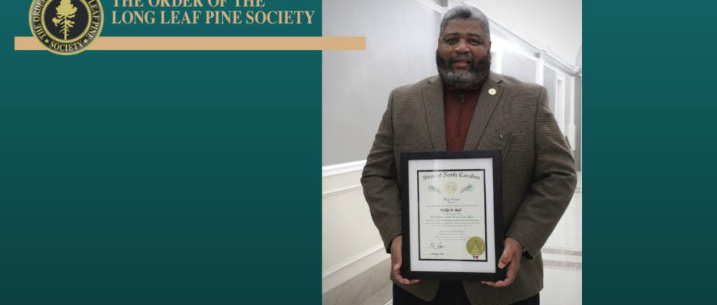Mayor Walker Reid holding the Long Leaf Pine plaque