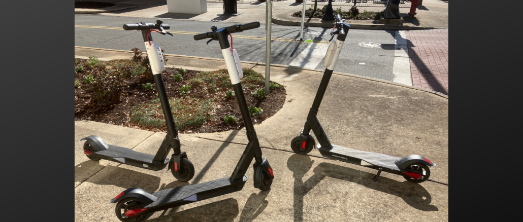 Three black, red and white scooters on the sidewalk