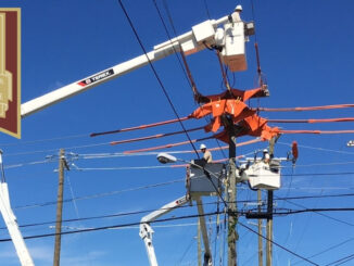 Three line workers in bucket trucks working on electric lines