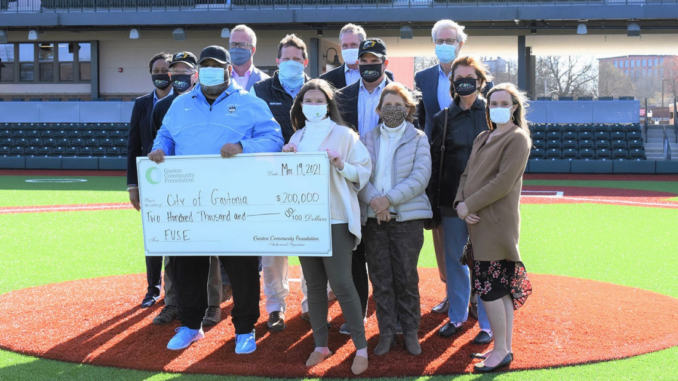 12 people standing at home plate with large ceremonial check