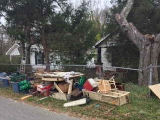 Discarded items piled at the edge of a yard