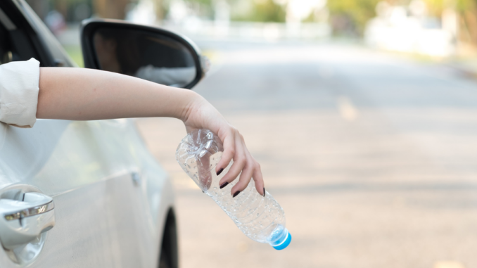 Woman about to drop empty bottle from car window