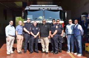 City officials and Fire Department employees in front of a firetruck