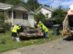 Three employees lift a discarded couch at the curb