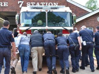 Fire and City officials pushing a firetruck into a fire station