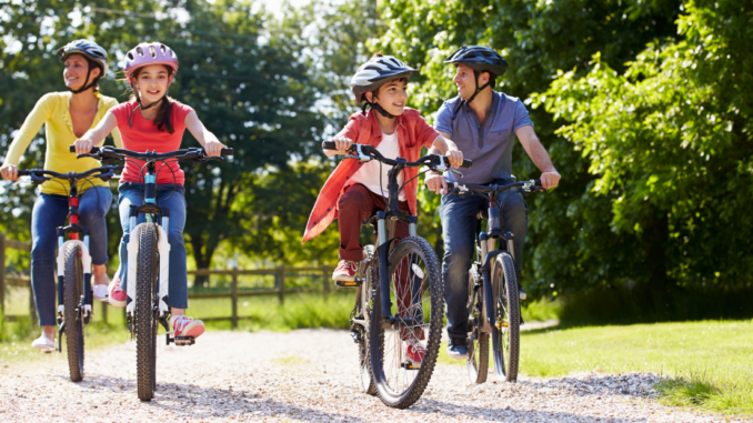 Parents and two children riding bicycles outdoors