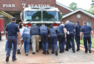 People pushing firetruck into station as part of ceremony