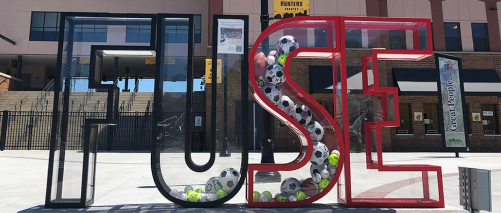 Clear plexiglass FUSE letters at ballpark filled with sports balls