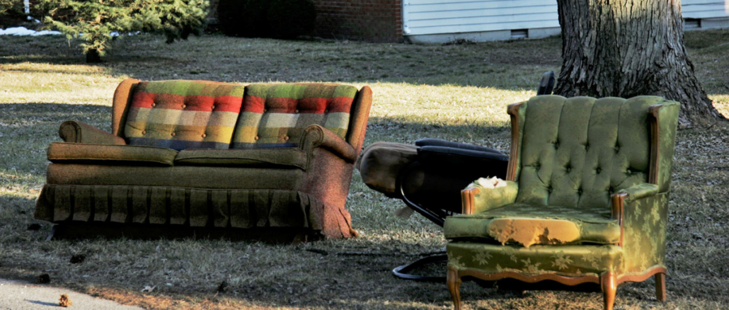 Couch and chair with tattered upholstery along street curb