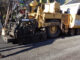 Big machine putting asphalt on street with employees assisting