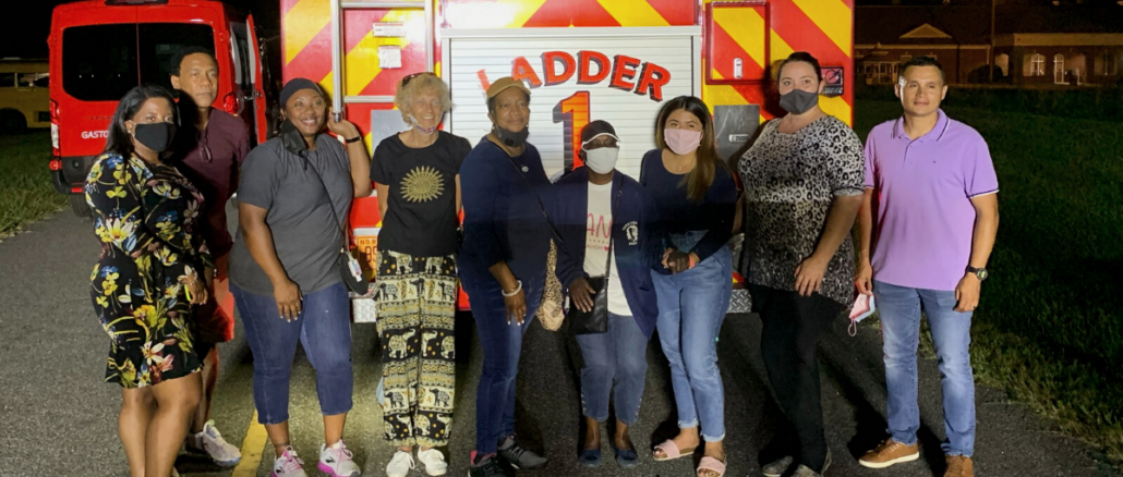 Nine members of Citizens Academy in front of the Ladder 1 firetruck